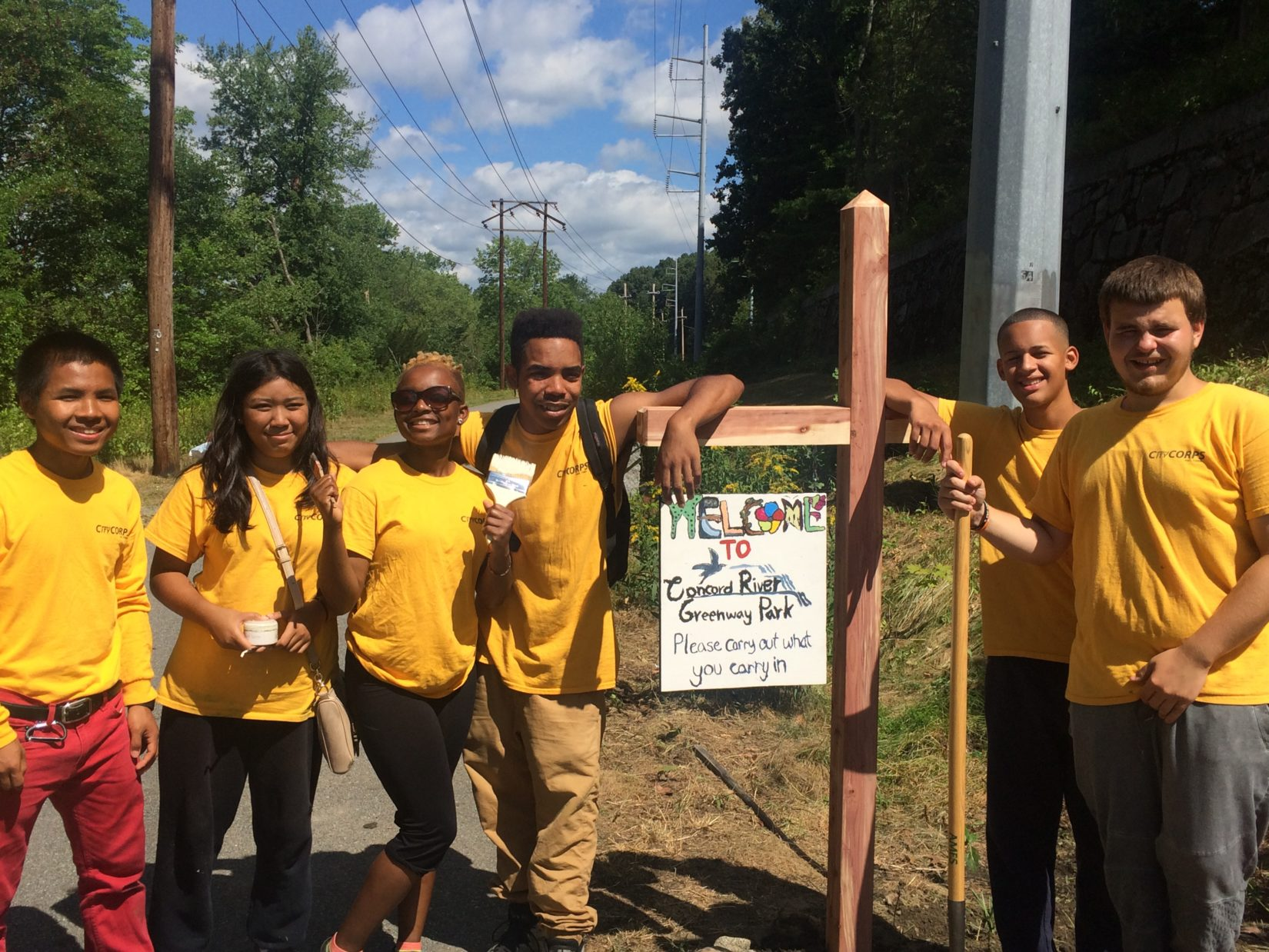 Spindle City Corps with their Concord River Greenway Sign