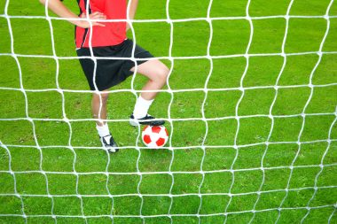 Soccer player with ball standing at goal net
